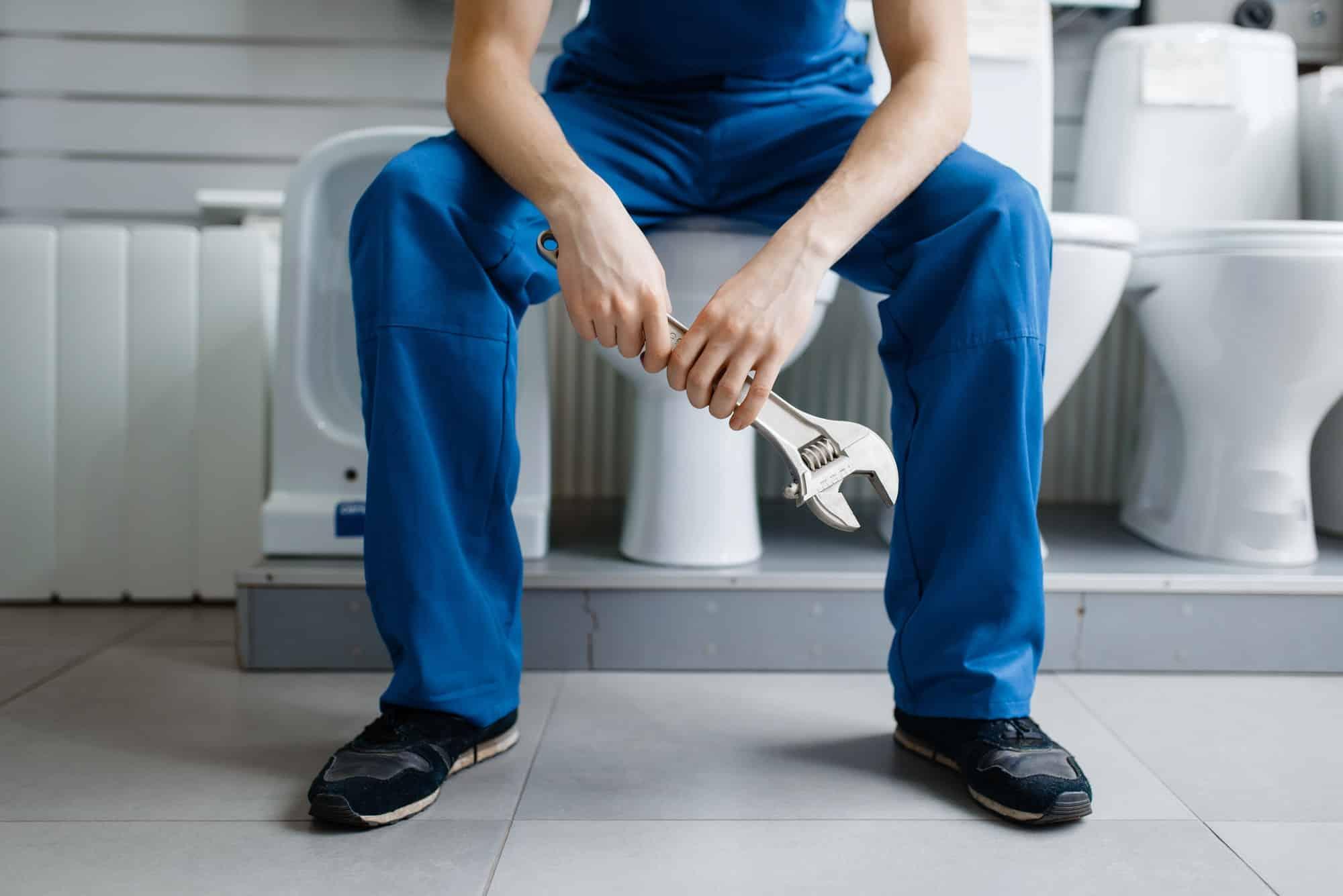 Plumber in uniform sitting on toilet in plumbering