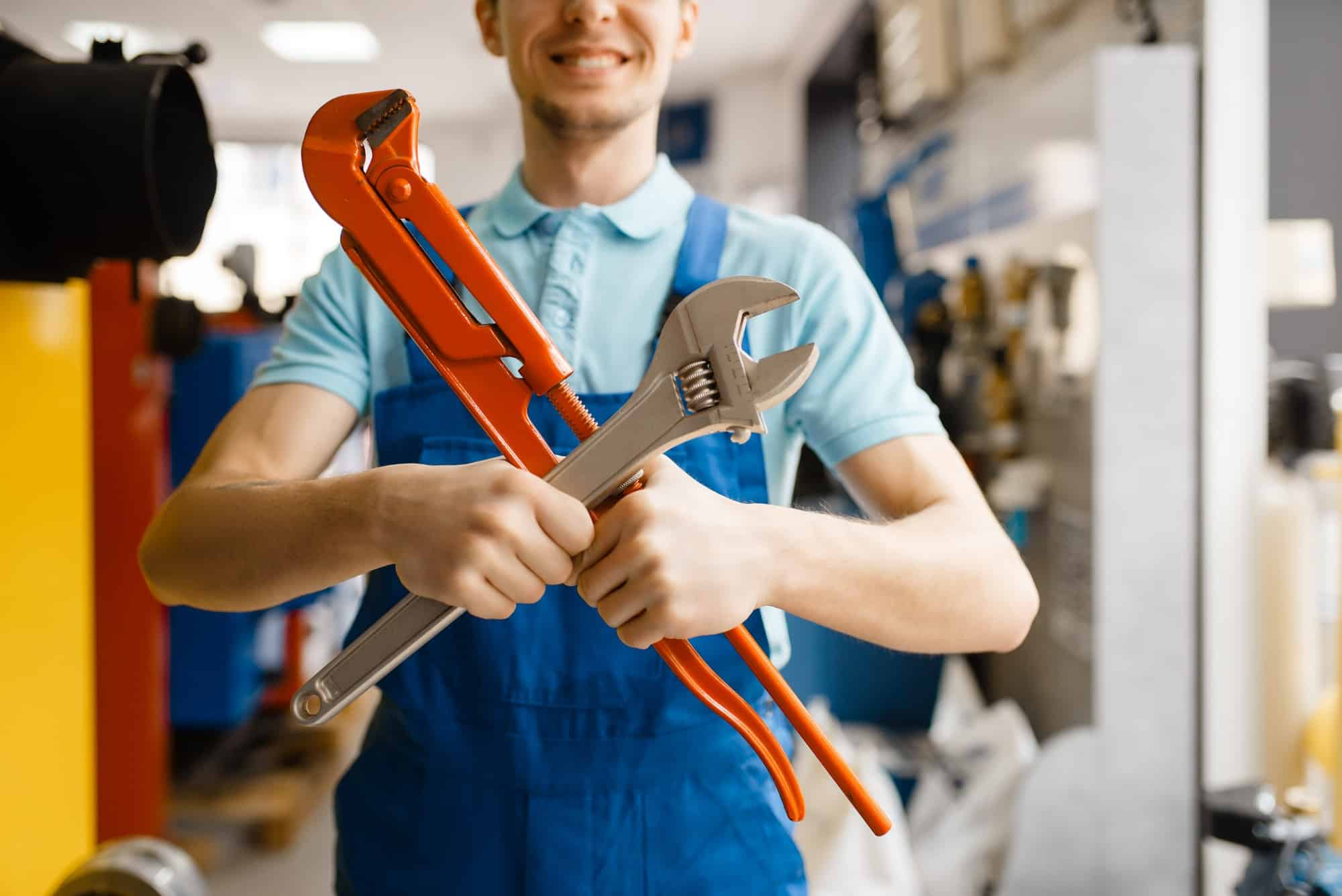 Plumber poses with pipe wrenches, plumbering store